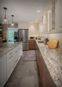 Burlington kitchen remodel showing island with flush stove top and base cabinets, perimeter cabinets with glass doors, and granite counters,.