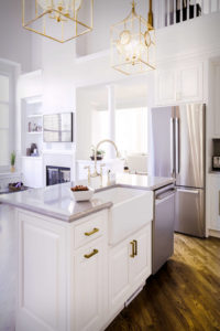 View of island rear with farmhouse sink and countertop, and inset cabinet doors.