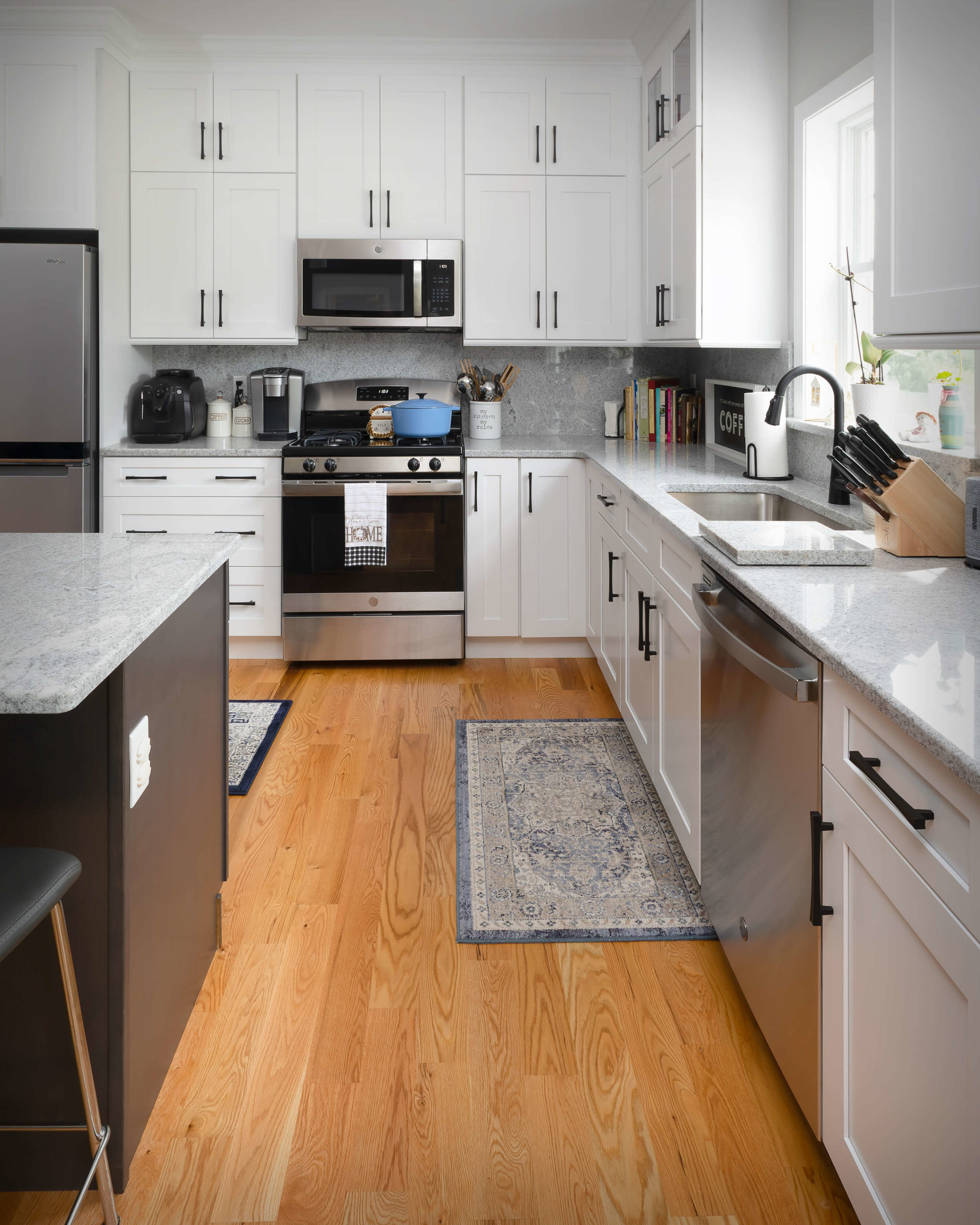 View of work surfaces featuring full height cabinets, matching drawer fronts, matching granite backsplash, and custom granite cutting board near sink in new kitchen and bathroom project in Middletown.