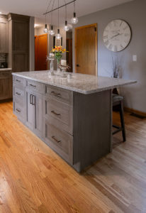 View of the Ultracraft island cabinets, Cherry Wood with Wicker Park door style and Coastal Grey stain finish, the eased edge on the Cambria New Quay quartz countertop.
