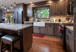 View to the in this Wallingford, CT kitchen remodel, showing Ultracraft Cherry Wood cabinets with Wicker Park door style in Coastal Grey stain finish and Cambria New Quay quartz counters.