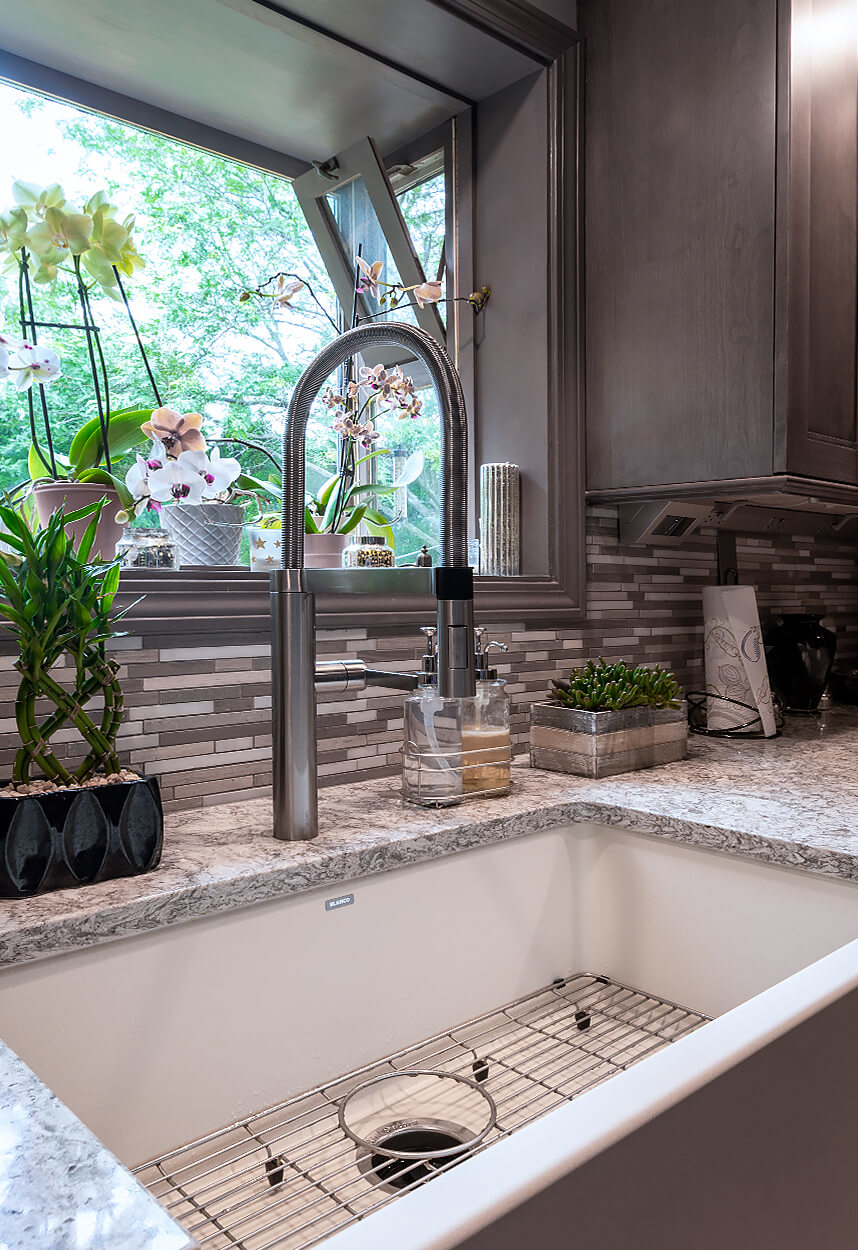View of the farmhouse sink with apron front, custom tile backsplash, and under cabinet power system from LeGrande.