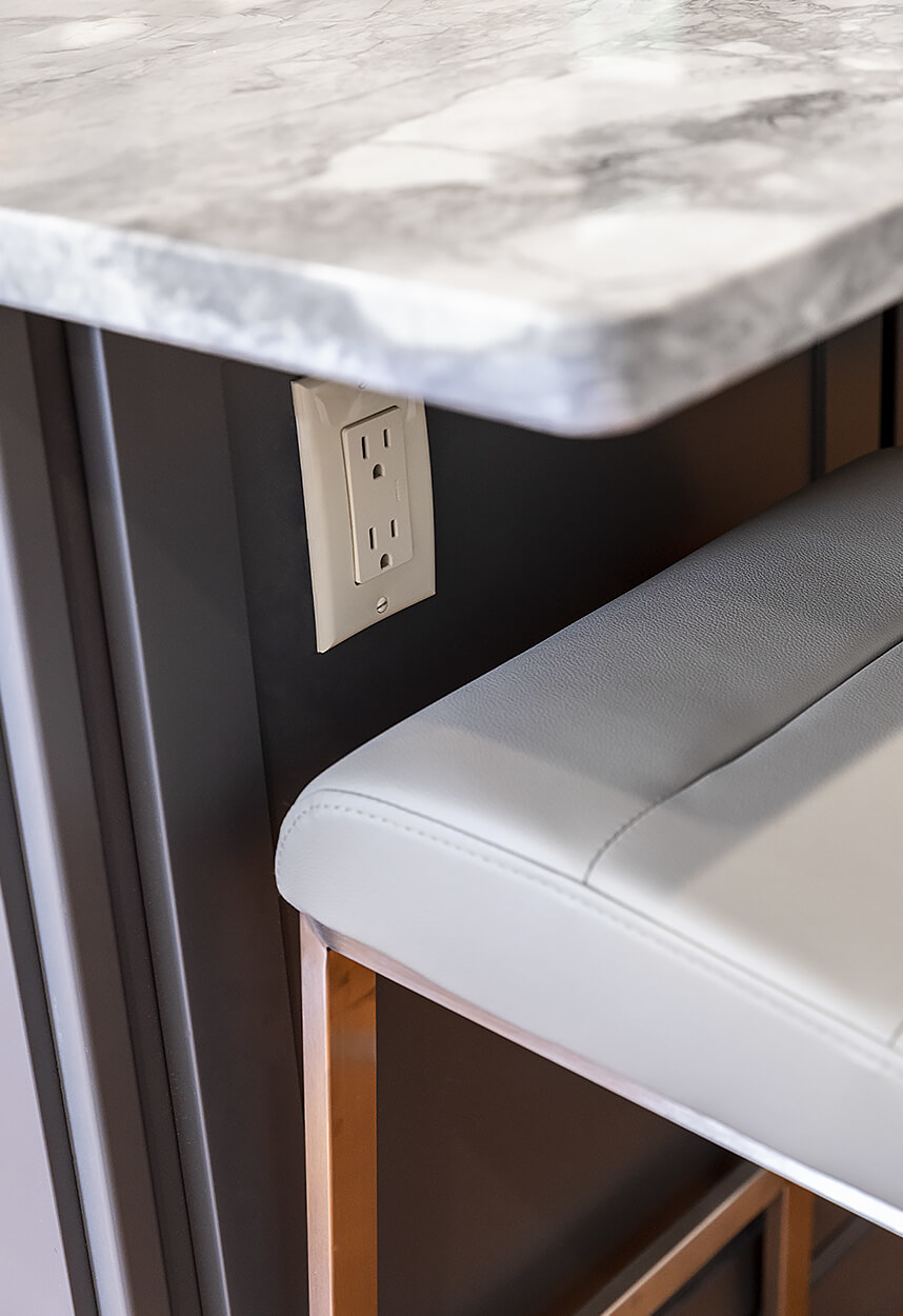 Detail of the island under-counter power, showing the beautiful patterns of the Super White Quartzite counter.