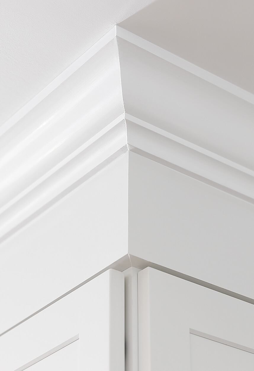Detail of the upper cabinets, showing custom crown moulding.
