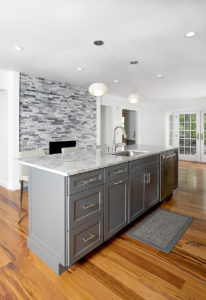 View of the island area and fireplace area AFTER work on this kitchen remodel in West Hartford.