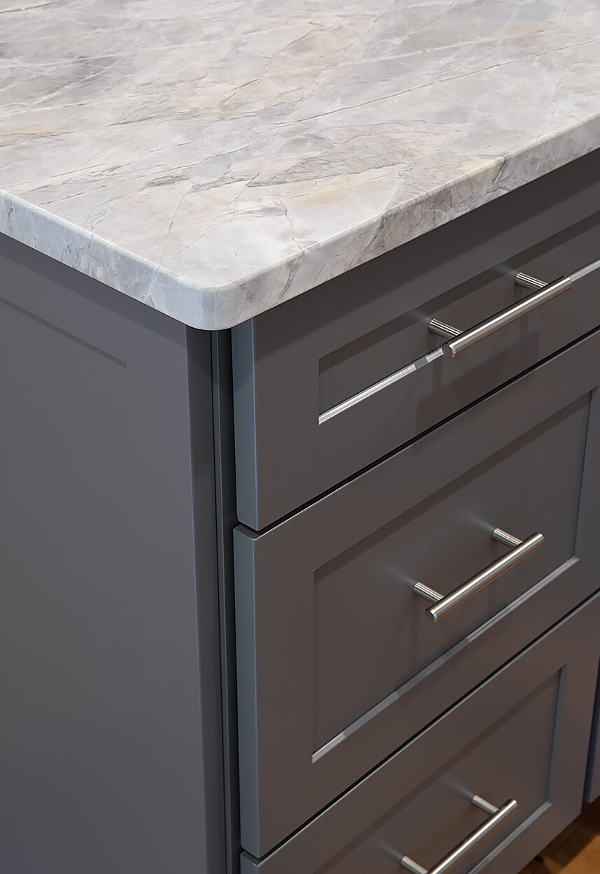 Detail of the matching drawer fronts and the beautiful patterns of the Super White Quartzite showing the custom eased edge.