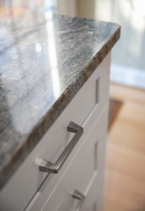 Detail of White Wave Granite counters with brushed nickel bar pulls by Richelieu.