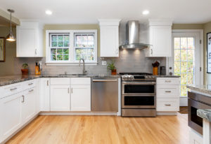 New kitchen cabinets and counters in this West Hartford kitchen remodel, with custom glass hood over the range.