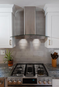 Custom glass range hood with custom upper cabinets designed to match.