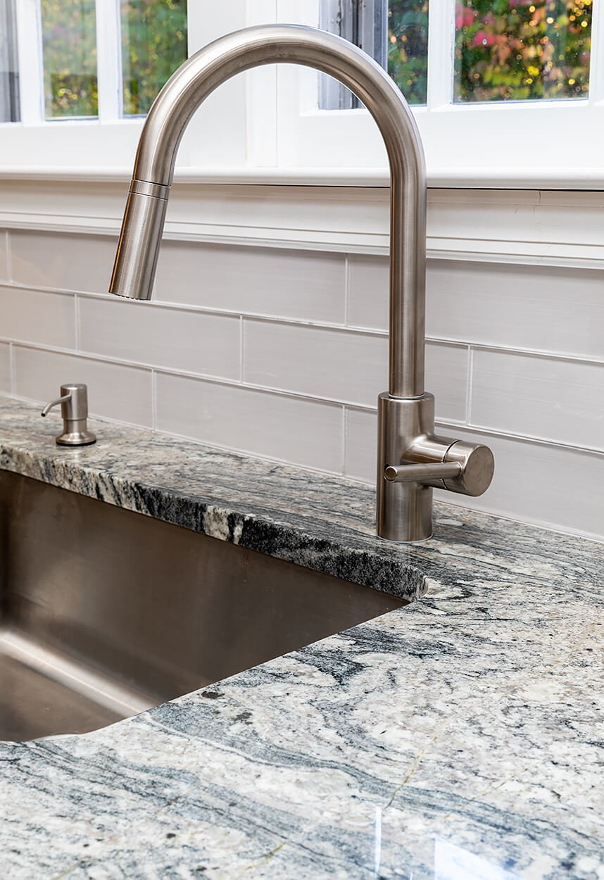 Detail of White Wave Granite counters and gray tile backsplash.